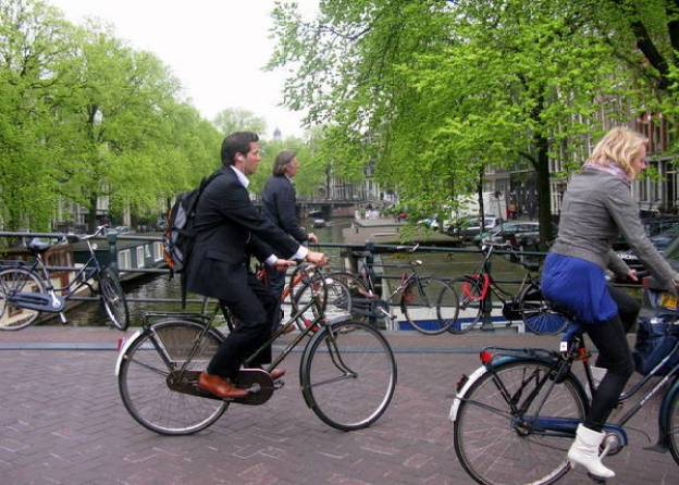 people riding bikes in amsterdam, the netherlands