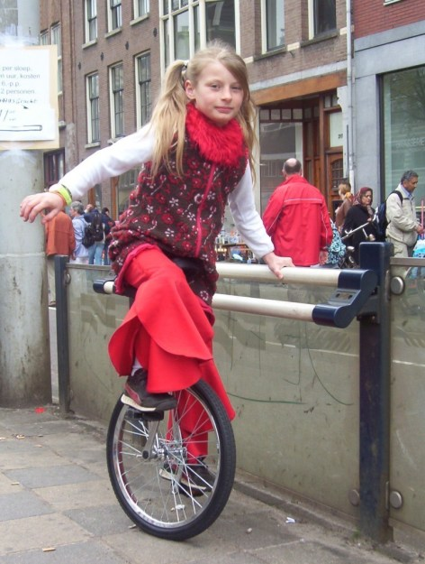 young girl on unicycle, amsterdam, the netherlands