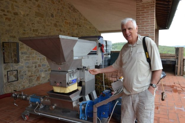 bob beside the grape crusher at il colombaio di cencio vineyard, gaiole in chianti, itay