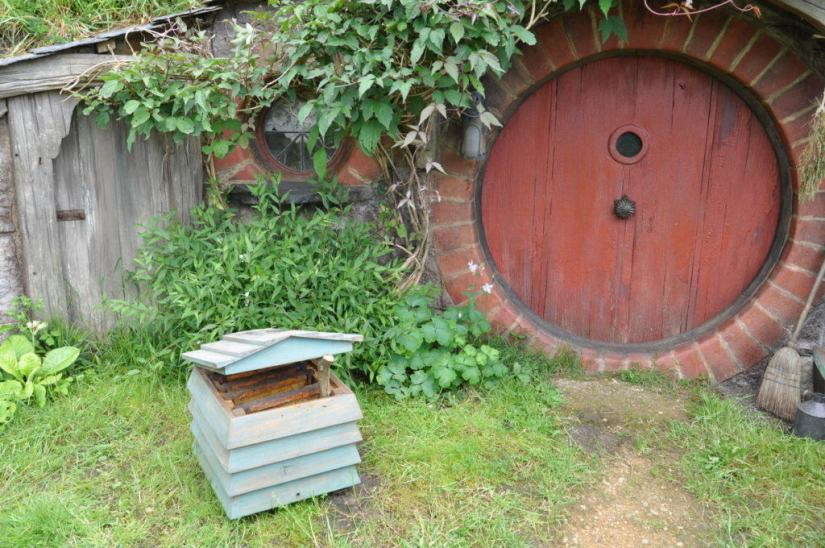 An image of an open beehive in front of the Beekeepers hobbit hole at Hobbiton in New Zealand. Photography by Frame To Frame - Bob and Jean.
