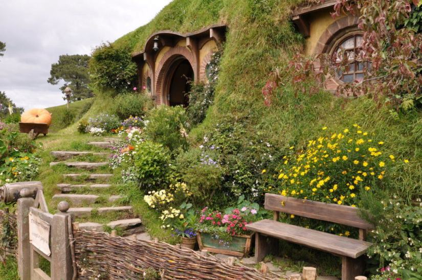 An image of the flower garden and stone steps our front of Bilboo Baggins Home at Hobbiton in New Zealand. Photography by Frame To Frame - Bob and Jean.
