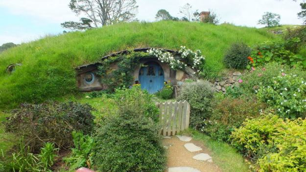 An image of a hobbit hole with a blue door in the side of a hill at Hobbiton in New Zealand. Photography by Frame To Frame - Bob and Jean.