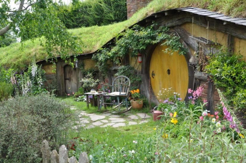 An image of a hobbit hole with a yellow door at Hobbiton in New Zealand. Photography by Frame To Frame - Bob and Jean.