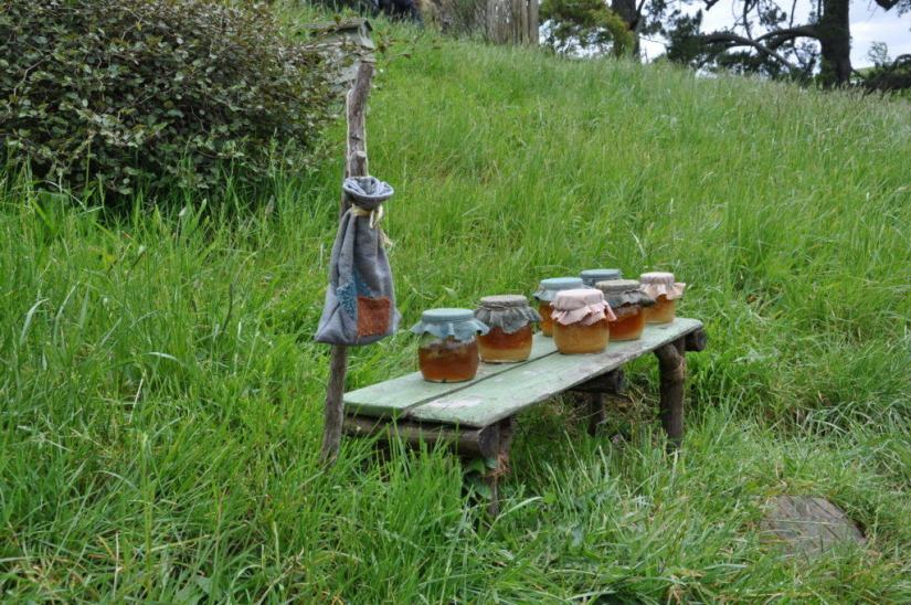 An image of seven jars of honey sitting on a wooden table at the home of shire beekeeper at Hobbiton in New Zealand. Photography by Frame To Frame - Bob and Jean.