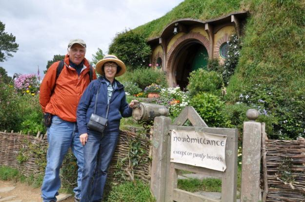 An image of Bob and Jean standing outside of Bilbo Baggins House at Hobbiton in New Zealand. Photography by Frame To Frame - Bob and Jean.