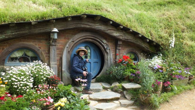 An image of a Jean opens a hobbit hole door at Hobbiton in New Zealand. Photography by Frame To Frame - Bob and Jean.