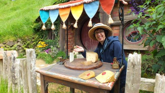 An image of Jean pretending to offer cheese for sale at a Hobbit hole in Hobbiton in Matamata, New Zealand. Photography by Frame To Frame - Bob and Jean