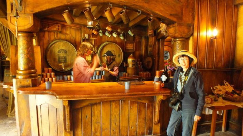 An image of Jean standing at the counter inside the Green Dragon Pub at Hobbiton in Matamata, New Zealand. Photography by Frame To Frame - Bob and Jean