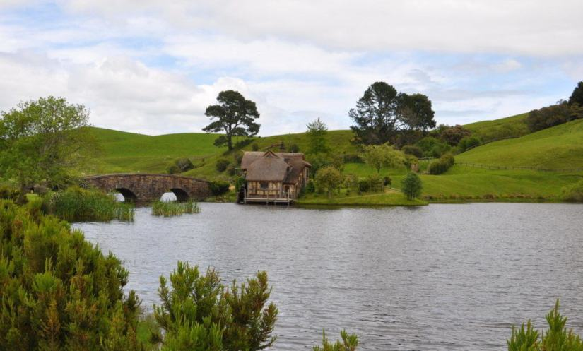 An image of the old water mill beside the stone bridge over the pond at Hobbiton in New Zealand. Photography by Frame To Frame - Bob and Jean.