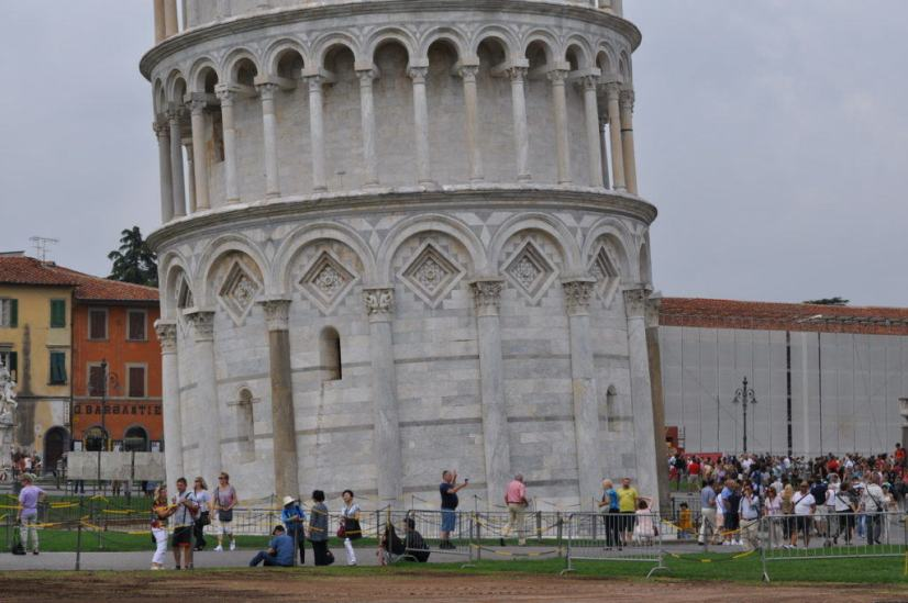 An image of people standing around the base of the Leaning Tower of Pisa in Tuscany, Italy. Photography by Frame To Frame - Bob and Jean.