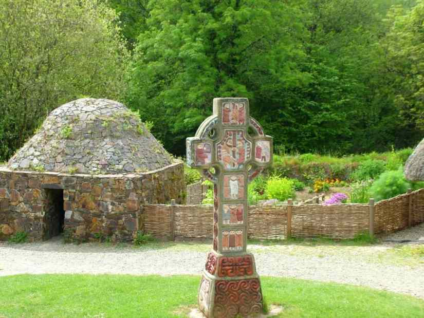 a Christian High Cross and beehive dwelling at Irish National Heritage Park, Ireland