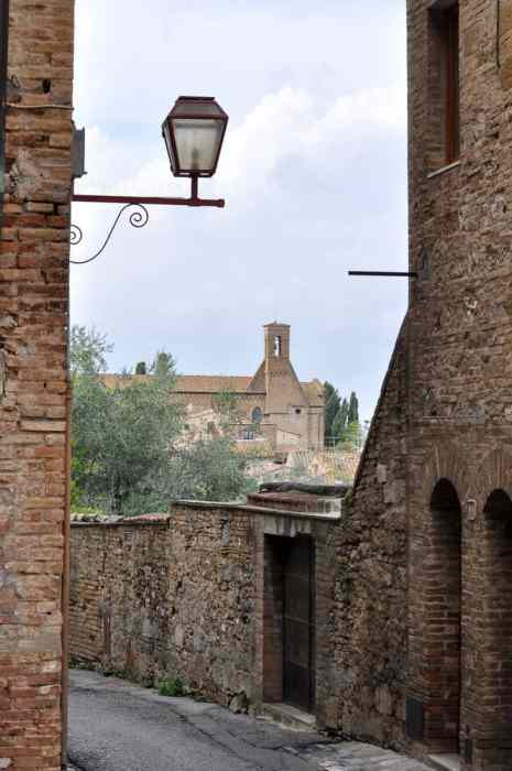 Image of stone walls and buildings inside San Gimignano, Italy.