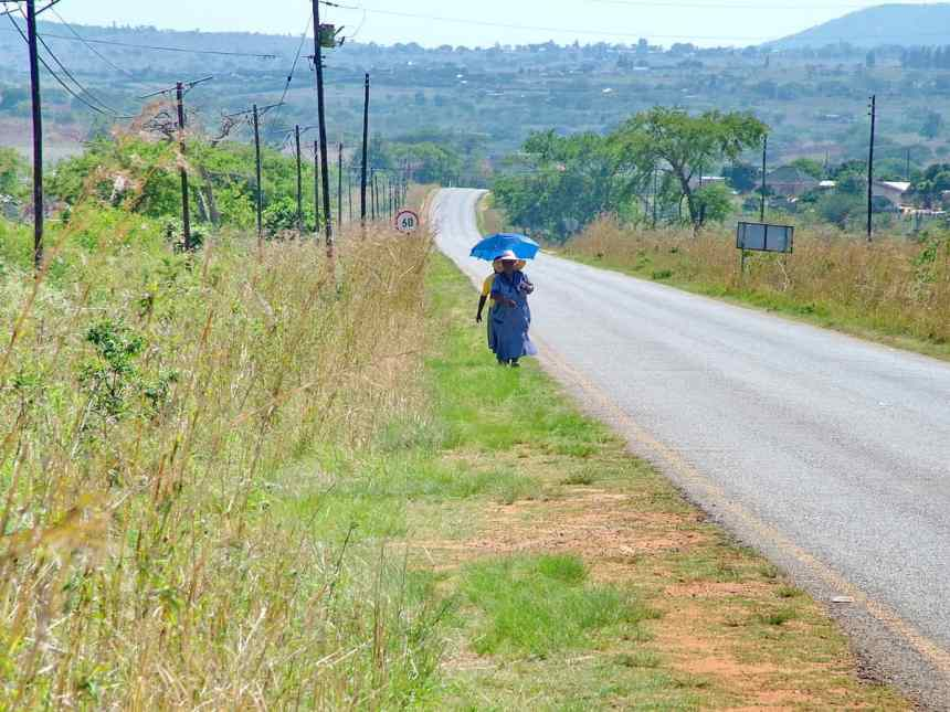 a lady walking along a paved road in swaziland, africa