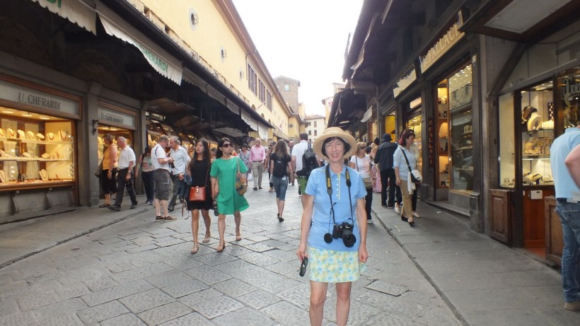 jean and shops on ponte vecchio, florence, italy