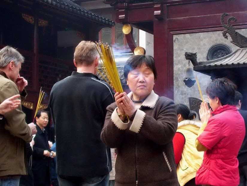 A woman prays to the gods will holding incense sticks inside the City God Temple of Shanghai.