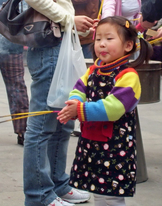 A young girl prays will holding her incense sticks outside the City God Temple of Shanghai.