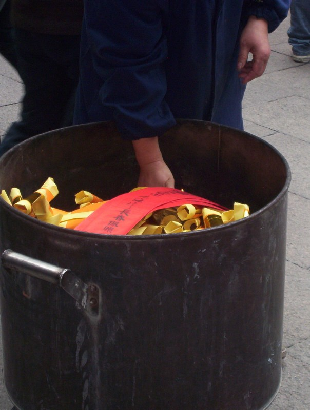 A container of red joss papers are carried to the burning pit inside the City God Temple of Shanghai in China.