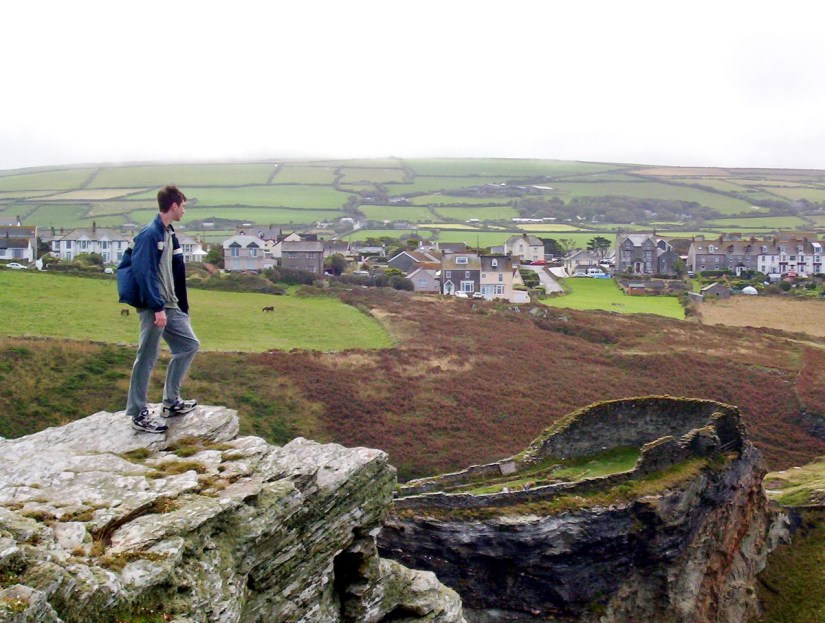 young lad looking at tintagel castle, cornwall, england