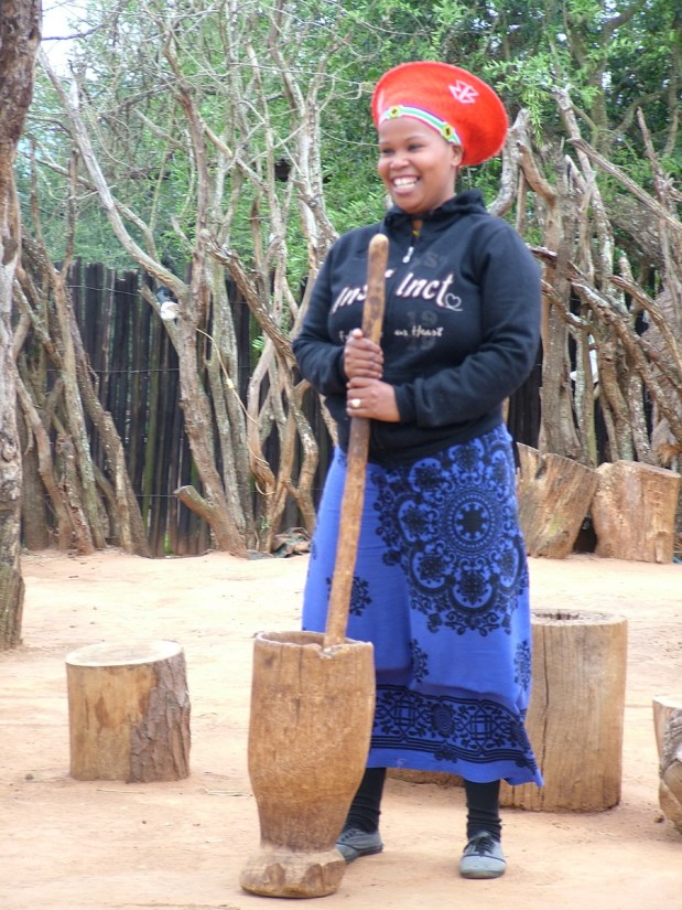 a married zulu woman grinding sorghum, shakaland, kwazulu-natal, south africa