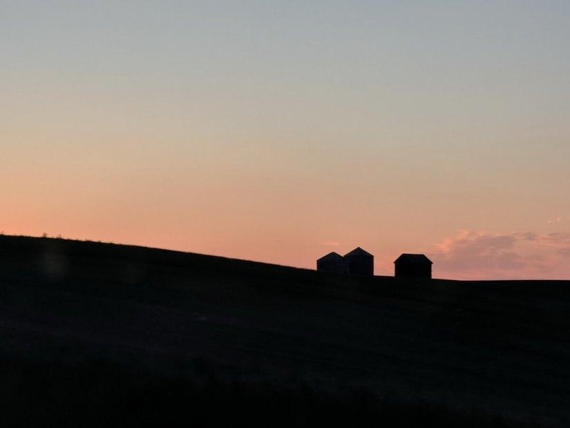farm buildings in silhouette against a pink sky, saskatchewan