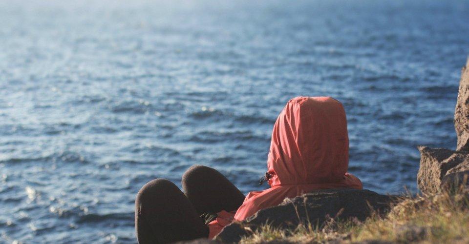 Persona in meditazione di fronte al mare