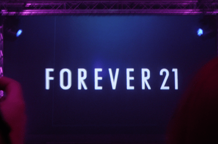 The forever 21 logo in white on a large black screen at the Forever 21 UK launch party in London