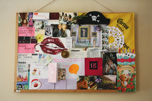 a noticeboard full of photographs, handwritten notes, birthday cards, travel parephenalia, post it notes, paintings, and various trinkets and gifts