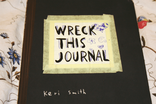 a copy of 'Wreck This Journal' by Keri Smith, with doodles on the front cover