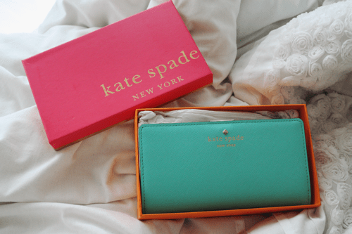 kate spade mikas pond stacy wallet in tiffany blue in kate spade packaging, on a floral white duvet