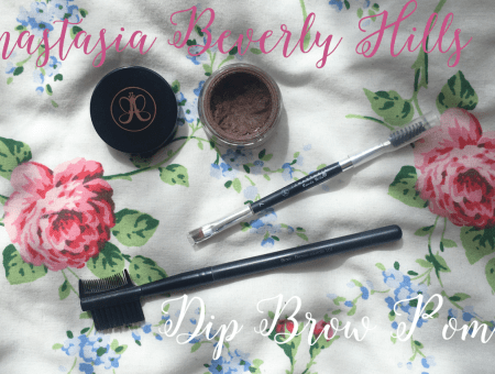 an open pot of anastasia beverly hills dipbrow pomade in 'taupe' lies next to the anastasia beverly hills dipbrow pomade brush and an eyebrow comb