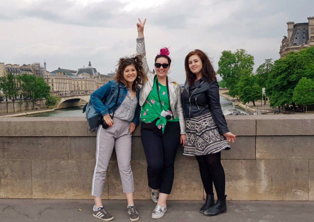 a picture of Chloe, Erica, and francesca of francescasophia.co.uk A row of Parisian houses on Monmarte in day trip to Paris on a budget on francescasophia.co.uk