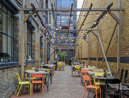 Outdoor seating area with orange and yellow chairs and hanging lights on francescasophia.co.uk