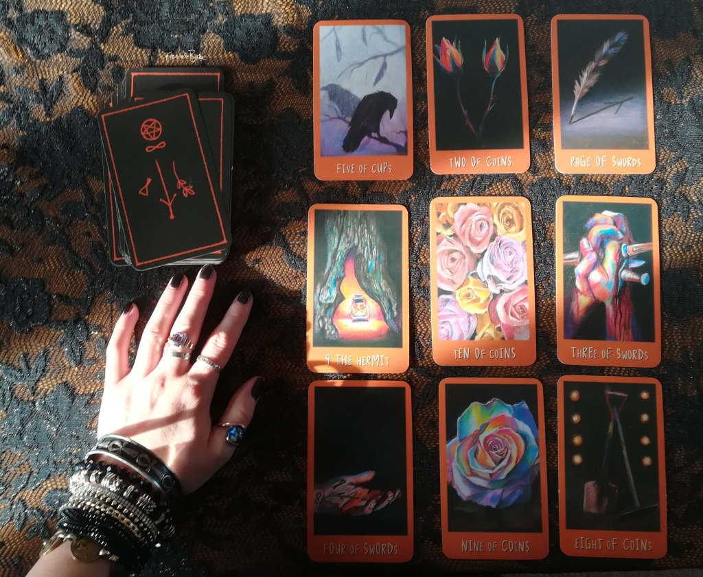 photograoh of Raven's Prophecy tarot by Maggie Stiefvater, next to hand
