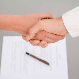 close-up shot of hands handshaking with a signed contract on the desk in background