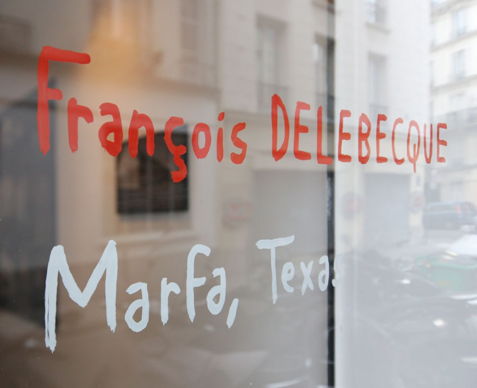 Annonce de l'exposition écrite à la main par Christian Roux sur la vitrine de la galerie.