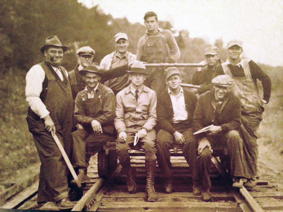 This is a picture of 10 men sitting on a manual rail-car, one of the men is Albini Vachon. It is black and white and the men have period clothes.