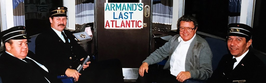 """This is a picture of Armand sitting with three other men. It features a homemade sign that reads """"Armand's Last Atlantic."""""""