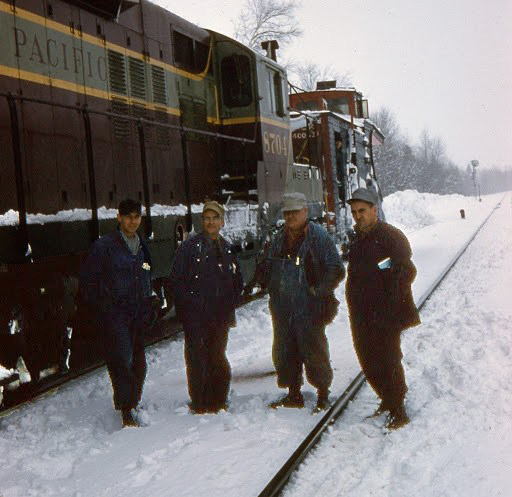 This is a picture of Armand standing next to a Canadian Pacific diesel train with three other men.
