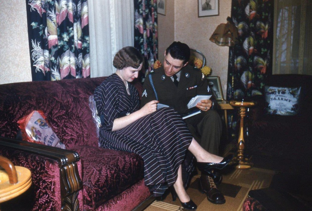 This is a photo of Armand in uniform sitting on a couch next to Lucette who wears a striped dress. They are looking at letters together.