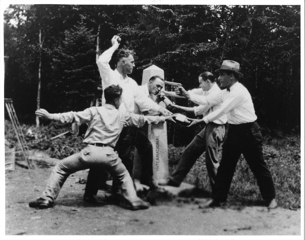 Photo of George, Susan's paternal grandfather and Susan's maternal grandfather Adelard along with three other men,  pretending to stick each other up at the Borderline