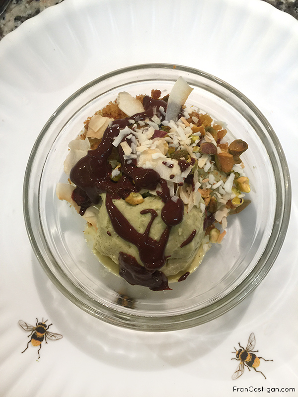 No Churn Avocado Lime Ice Cream garnished fully with cake crumbs. pistachios, coconut, and chocolate ganache