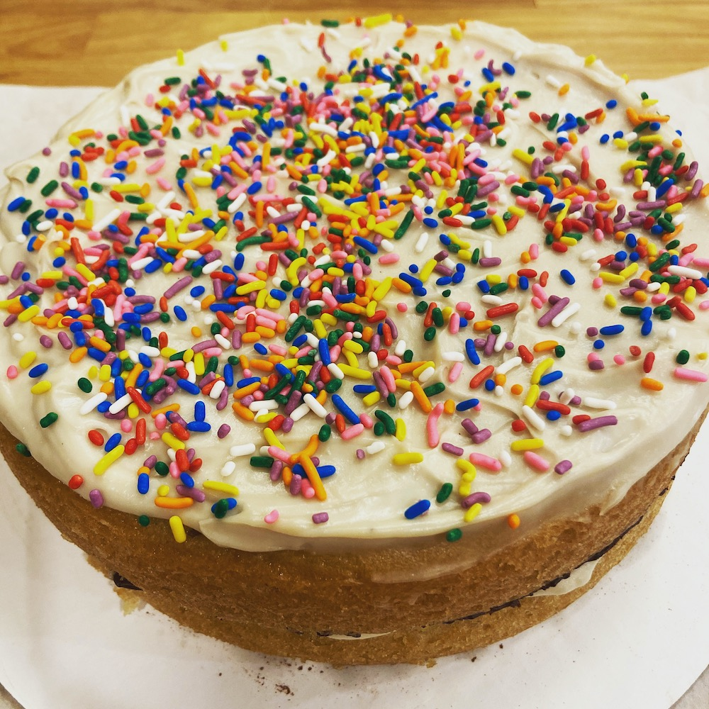 Vegan birthday cake topped with vanilla pastry cream and sprinkles