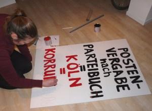 "Foto: Frau malt Protestplakat: ""Postnvergabe nach Parteibuch = Köln = Korruption"