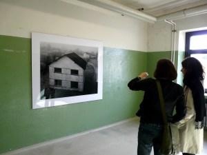Foto: Zwei Besucherinnen betrachten ein Bild in einem Kasernengebäude