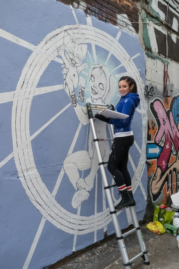 Street Artist Aurora works on her piece in the thriving Kensington Market area of Toronto.