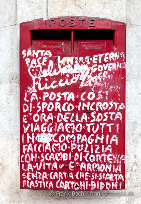 Old red postbox decorated with grafitti