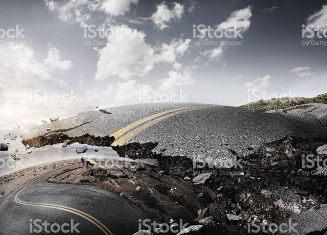 earthquake-crashed-desert-road-cracked-asphalt-picture-id481567106.jpg