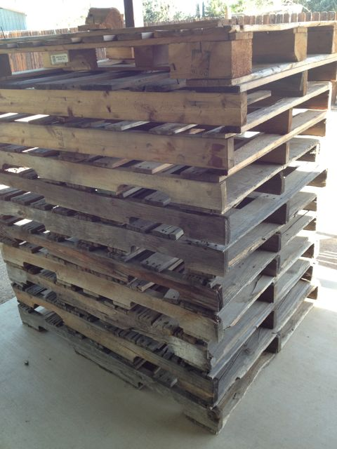 A stack of wooden pallets on a cement patio.