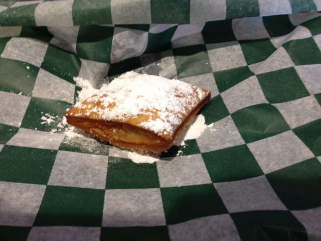 Beignet with powdered sugar on green and white checkerboard paper