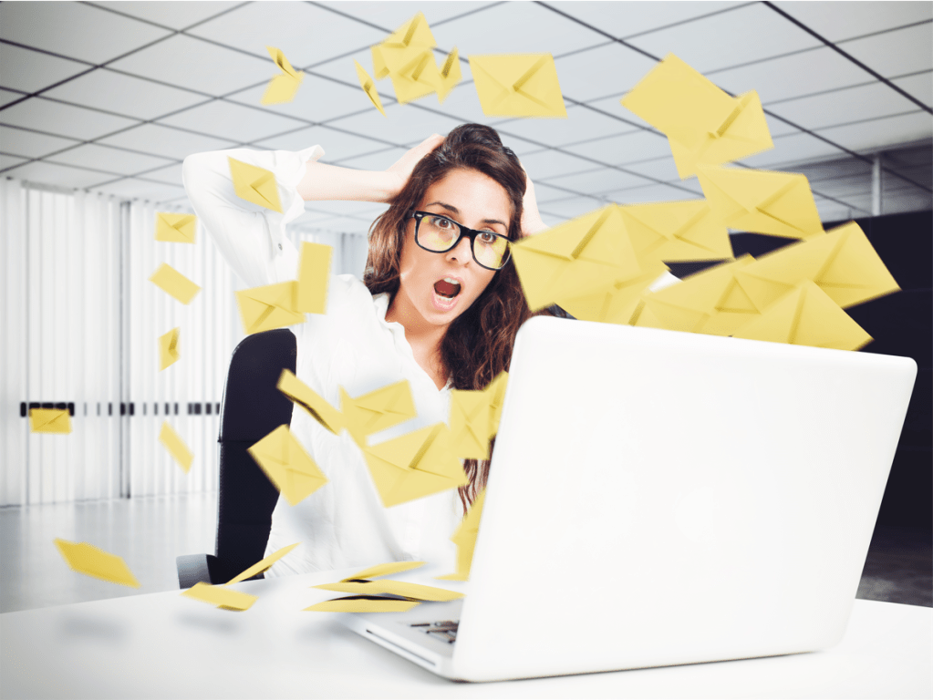 Woman at desk with dozens of email envelopes coming out of her computer